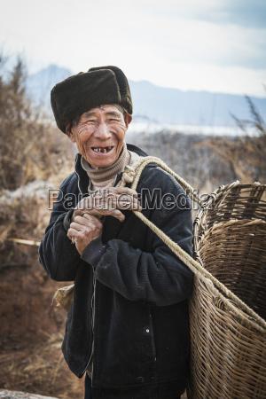 naxi chinese man carries basket lijiang