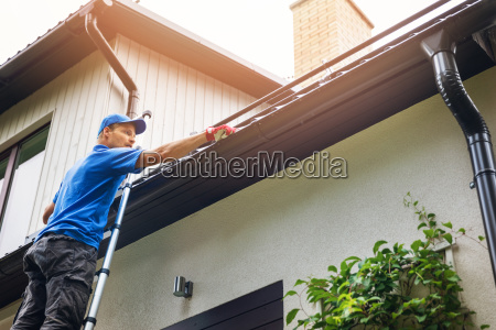 man on ladder cleaning house gutter