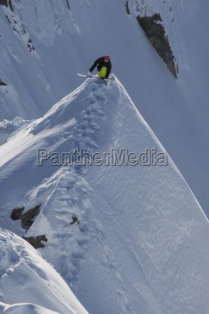 snowboarder balancing on extreme mountain ridge