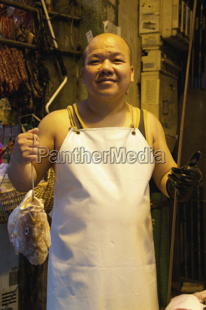 smiling chinese fishmonger in apron holding