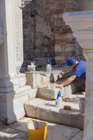 a male archeologist works with fine