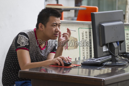 man smoking on a computerhongcunanhuichina