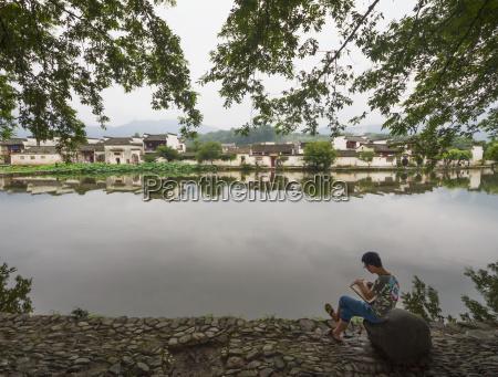 painter by nanhu lake hongcun anhui