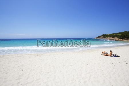 couple sunbathing on white sand beach