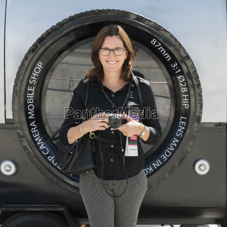 a woman stands holding her camera