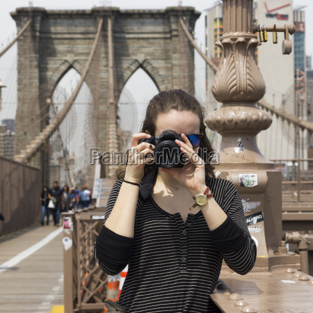 a young woman holds a camera