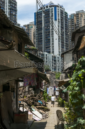old neighborhood surrounded by skyscrapers chongqing