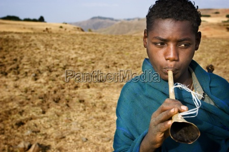 boy blowing horn in field ethiopia