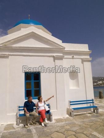 senior couple sitting outside orthodox church