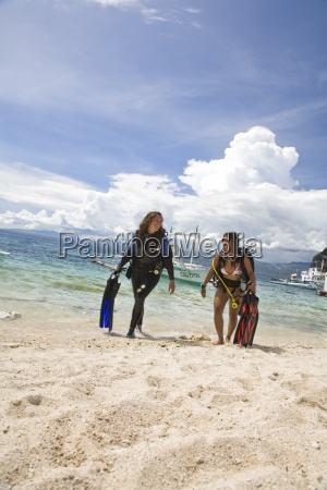 young woman with diving equipment walking