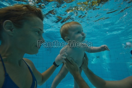 parents assisting baby to swim underwater