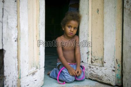 young girl kneeling in doorway neiba