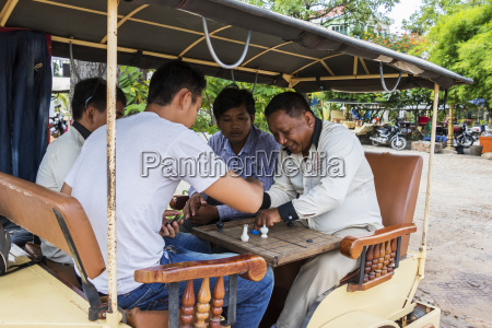 cambodian men playing a board game