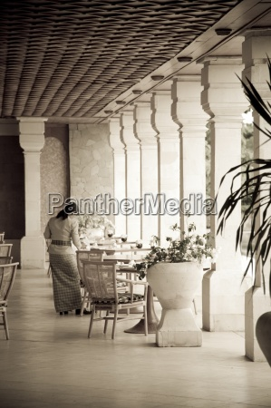 waitress setting table in restaurant toned