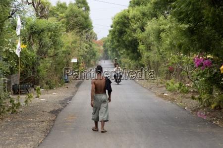man walking on road in bali