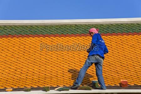 man repairing roof of wat pho