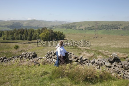couple embracing by rustic stone fence