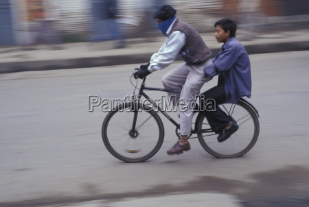 two men riding a bike