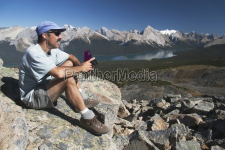 male hiker resting with water bottle