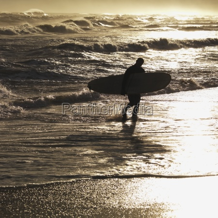 silhouette of man carrying surfboard sag