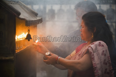 woman lighting candles at a shrine