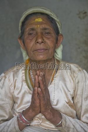 elderly woman praying pokhara nepal