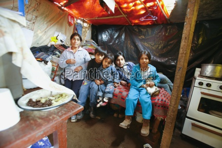 family in poverty stricken dwelling lima