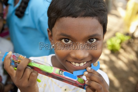 a child holding a new toothbrush