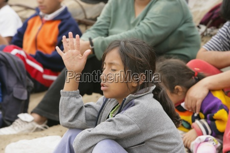 young girl raising hand lima peru