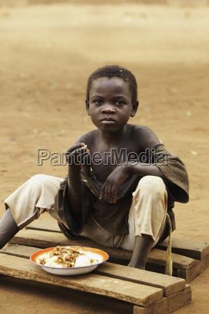 a boy eats a meal sitting