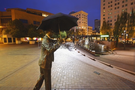 a male statue with an umbrella