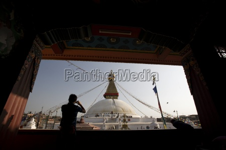 man taking a picture of boudhanath