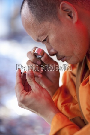 buddhist monk looking through magnifying glass