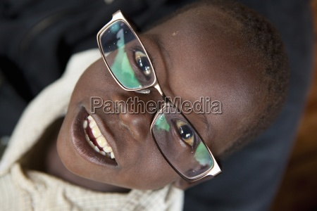 a boy wearing adult sized glasses