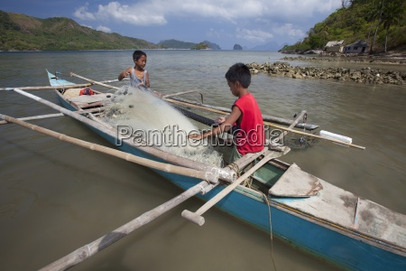 two young filipino boys work on