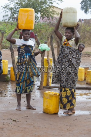 two women carry large water jugs