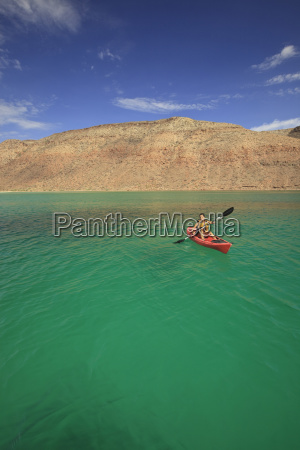 a tourist paddles a boat off