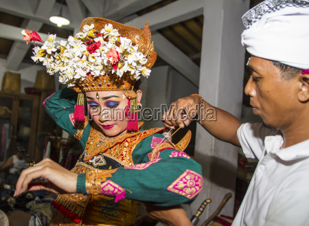 balinese man assisting a dancer of