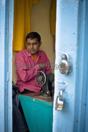 a man sits at a sewing