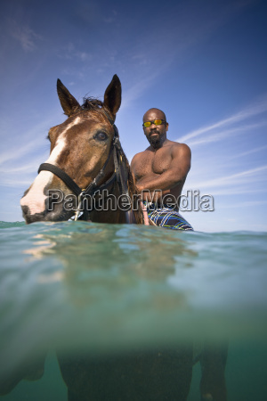 a man swims with a horse
