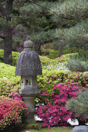 a stone lantern with flowers and