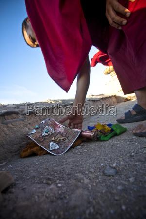 a ladakhi monk reaches for his