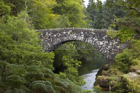 a stone bridge crossing a river