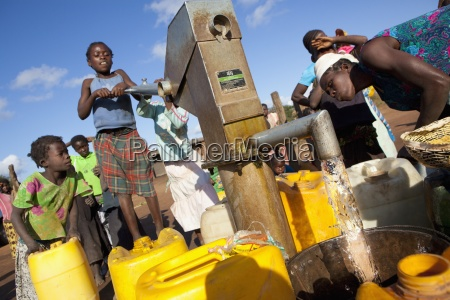 a young girl pumps clean water