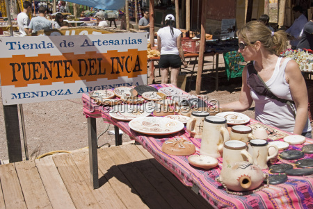 female tourist examining native art on