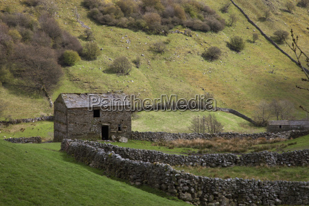 a stone shed in a field