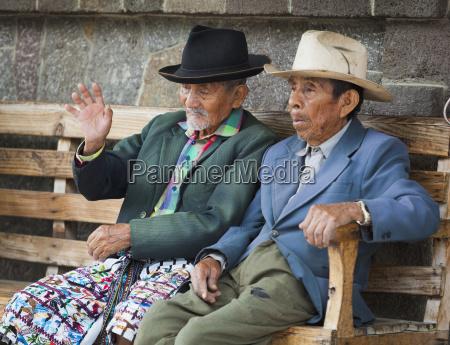 two senior men sit together on