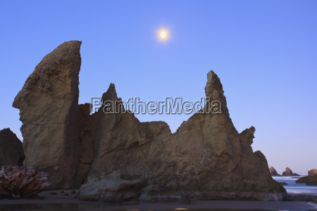 moon set over rock formations at