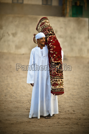 a muslim man carrying a rolled