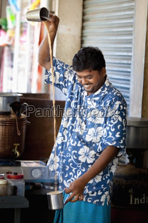 a man pouring a beverage from
